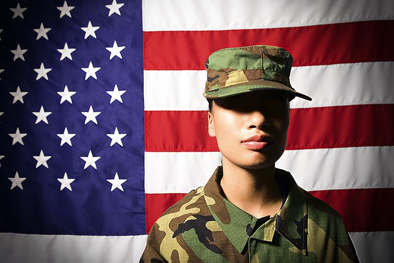 A service member with American flag in the background